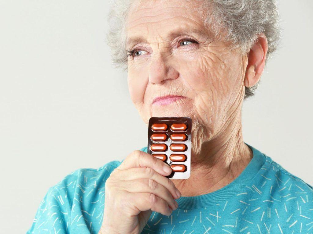 senhora idosa pensa na cura do alzheimer segurando uma cartela de comprimidos